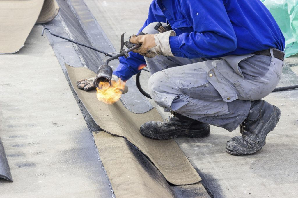 roofer putting on roof seals with blow torch