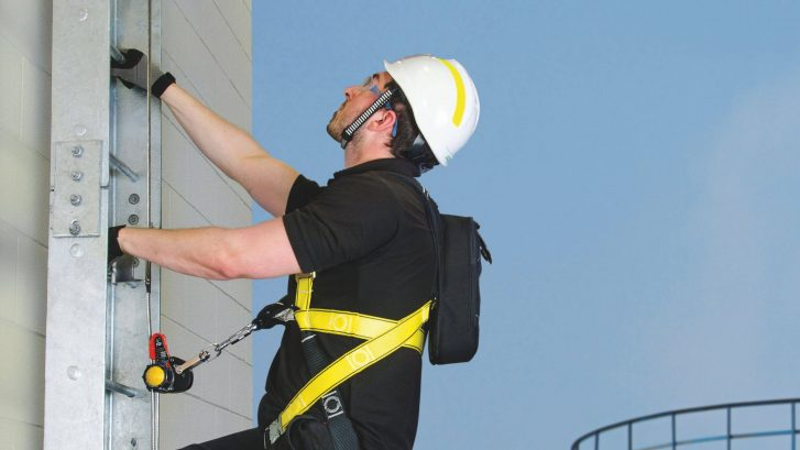 Workman demonstrating a vertical cable banner on ladder
