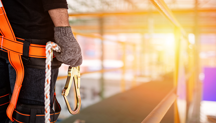 man holding fall protection locking carabiner